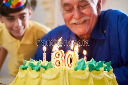 boy and senior man blowing candles