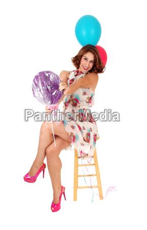 glueckliche frau mit zwei luftballons