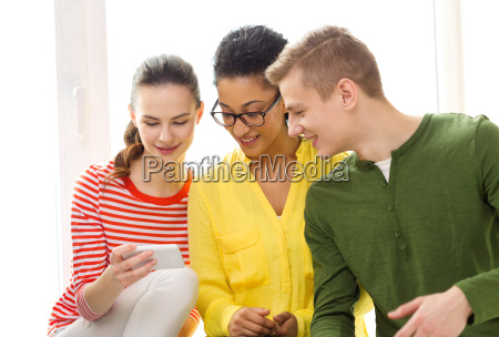 drei laechelnde studenten mit dem smartphone