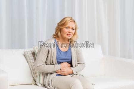 unglueckliche frau leidet unter magenschmerzen zu