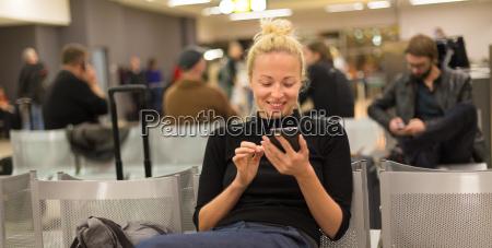 lady mit smartphone waehrend bei airpot