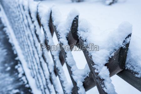 schnee auf einem zaun aus holz