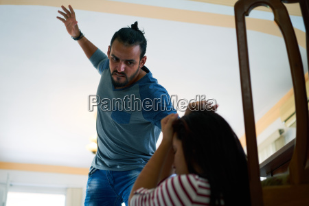 man fighting with scared woman at
