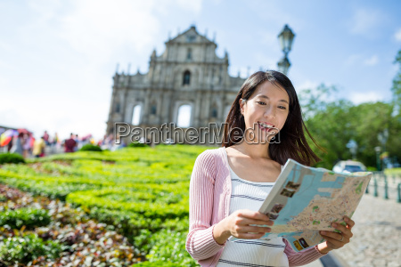 young woman using city map in