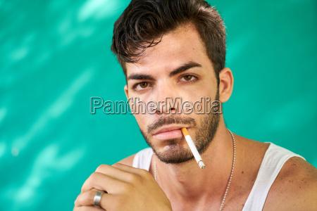 portrait of young hispanic man smoking