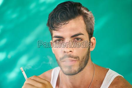 young hispanic man smoking cigarette and