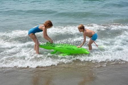 zwei kinder spielen am meeresstrand mit