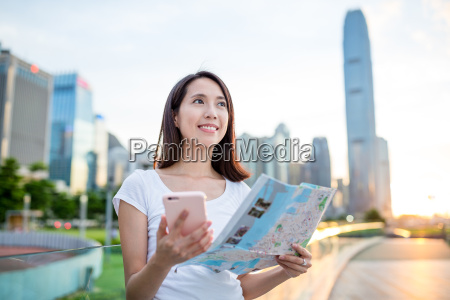 woman using city map and mobile