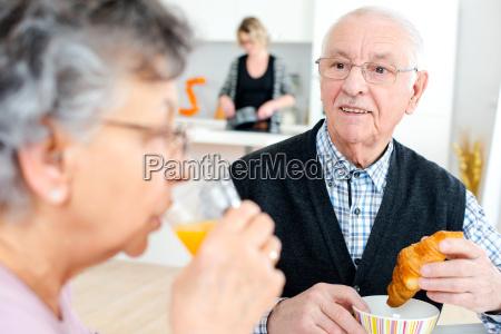 gluecklich senior paar mit glaesern orangensaft