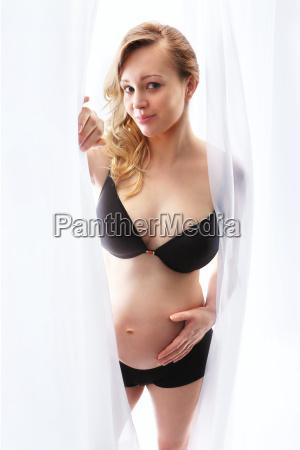 schwangere frau in schwarzer unterwaesche