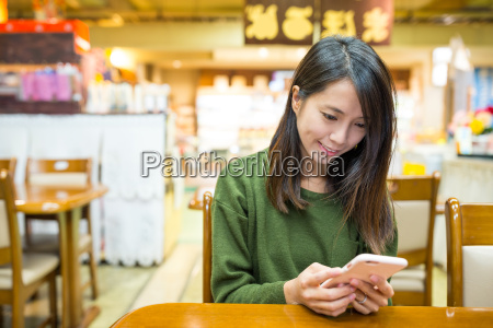 woman using cellphone in japanese restaurant
