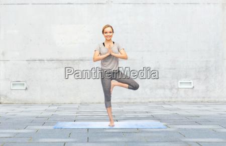 frau macht yoga in baum pose