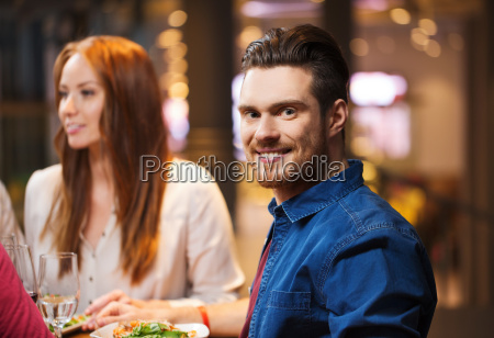 happy man with friends having dinner