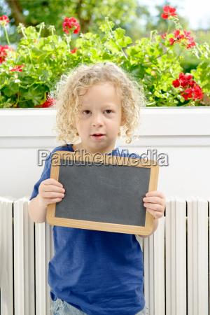 little blond boy holding school blackboard
