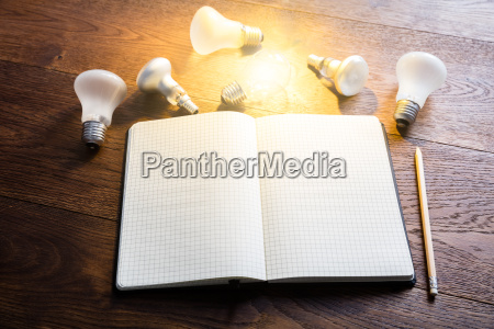notebook with glowing light bulbs on