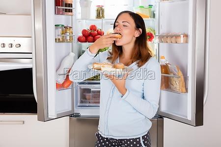 woman eating sweet food near refrigerator