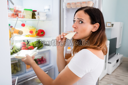 woman eating cheese in front of