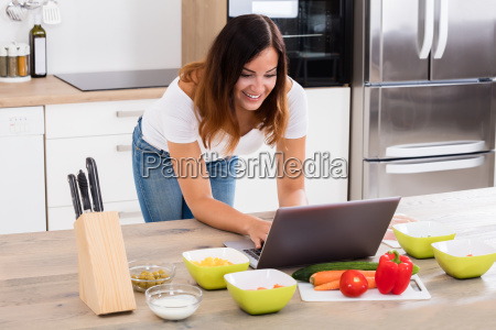 smiling woman using laptop in kitchen