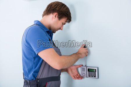 repairman fixing security system