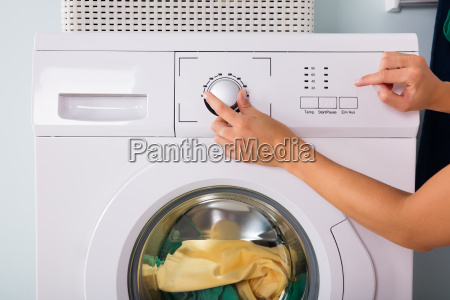 person hand pressing button of washing