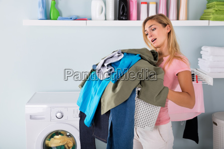 woman holding a bucket of clothes