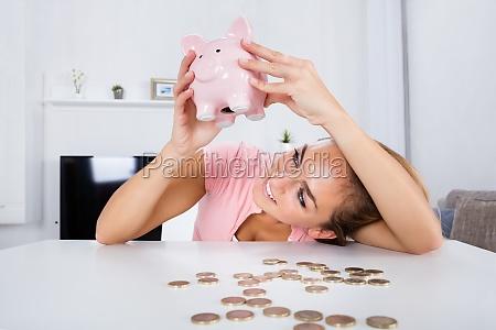 happy woman emptying her piggybank savings