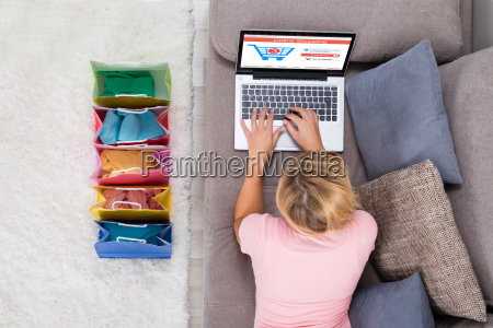 woman lying on sofa using laptop