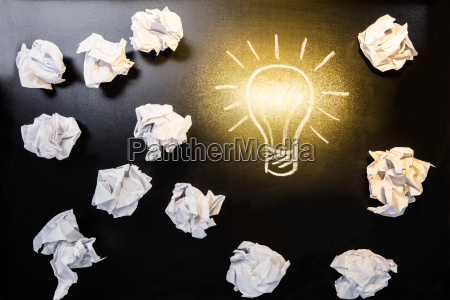 crumpled paper with illuminated light bulb