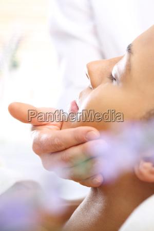 entspannende gesichtsmassage frau in einem wellness