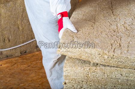 attic loft insulation man holding rock
