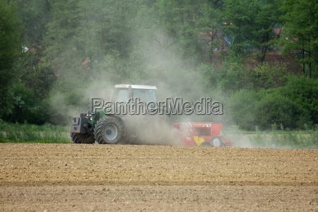 traktor faehrt auf einem braunen feld