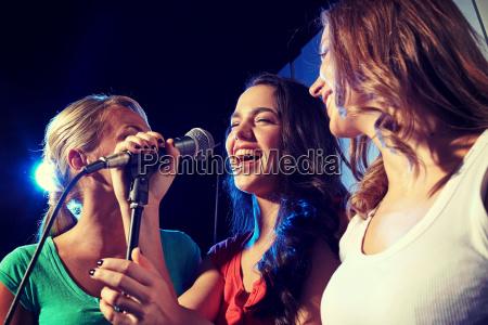 glueckliche junge frauen singen karaoke im