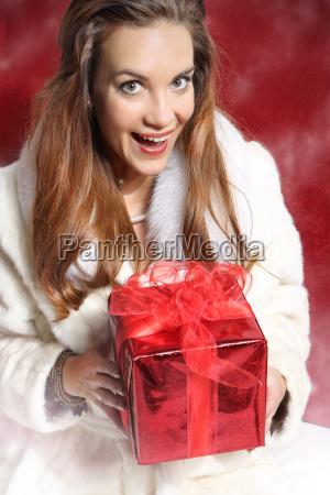schoene elegante frau mit rotem geschenk