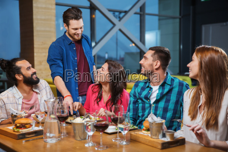 friends dining and drinking wine at