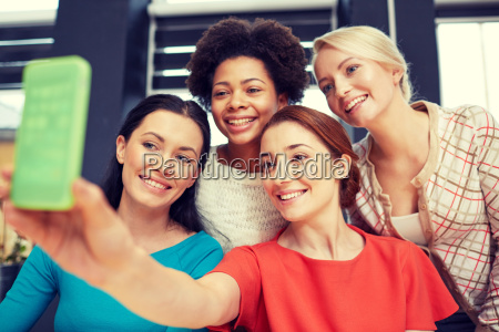 happy young women taking selfie with