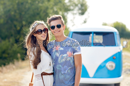 smiling young hippie couple over minivan