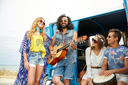 happy hippie friends playing music over
