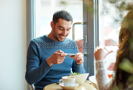 happy couple picturing food by smartphone