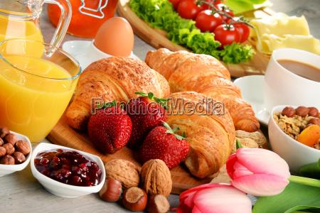 fruehstueck mit croissants kaffee obst orangensaft