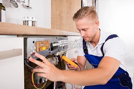 male technician fixing dishwasher