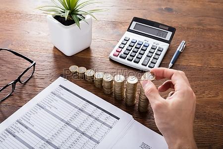 person stacking muenzen auf schreibtisch