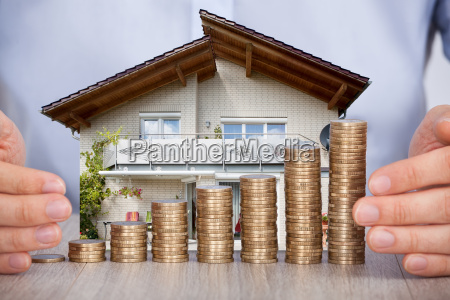 businessmans hand protecting euro coins at