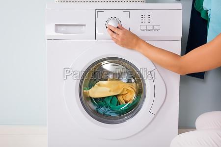 person hand druecken taste der waschmaschine