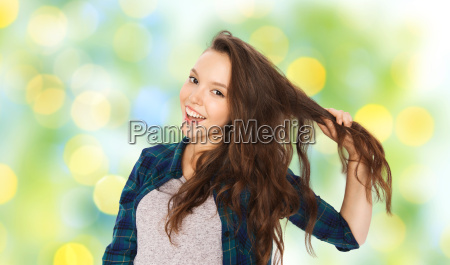 happy teenage girl holding strand of