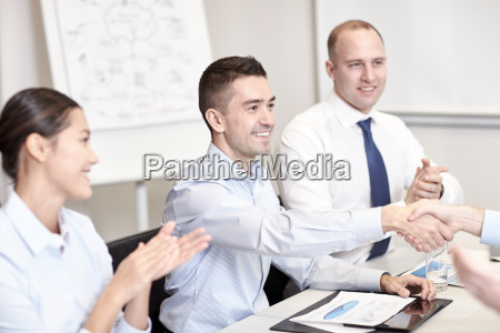 smiling business team shaking hands in