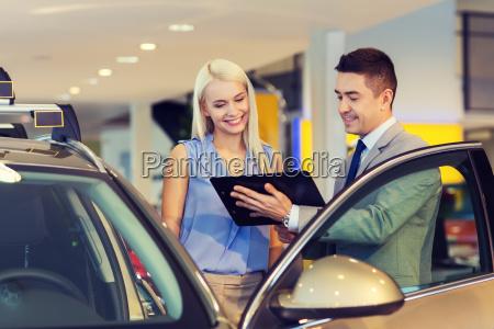 glueckliche frau mit autohaendler in auto