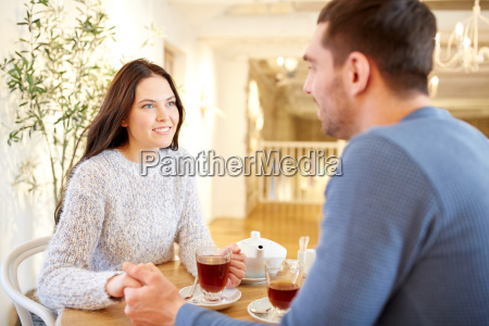happy couple with tea holding hands