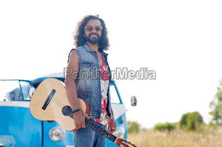 hippie man with guitar over minivan