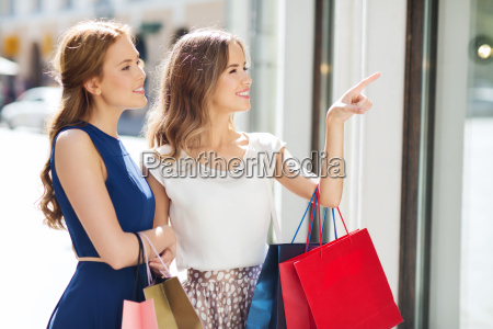 happy women with shopping bags at