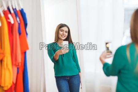 woman with smartphone taking mirror selfie